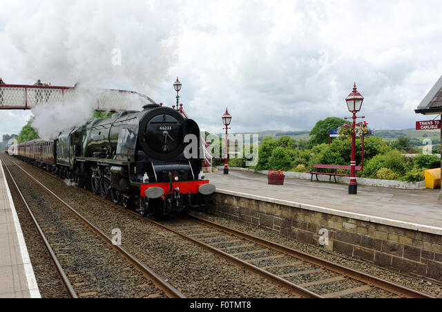 The LMS Princess Coronation Class 46233 Duchess of Sutherland steaming through Settle station en route to Carlisle - Stock Image