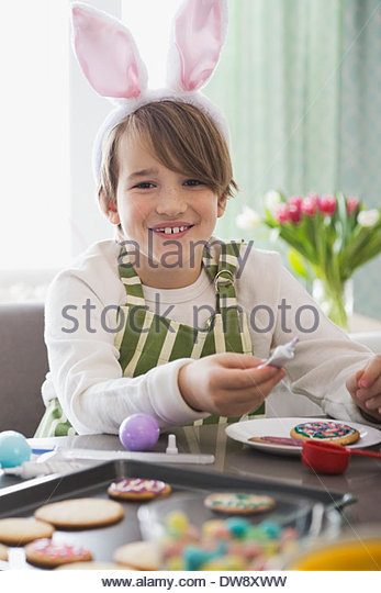 Portrait of boy wearing rabbit ears decorating Easter cookies - Stock Image