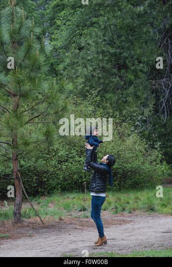 Mid adult woman holding up toddler daughter on forest path, Yosemite National Park, California, USA - Stock Image