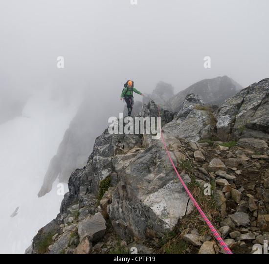 Female climber crossing rock ridge, Picket Pass, North Cascades National Park, WA, USA - Stock Image