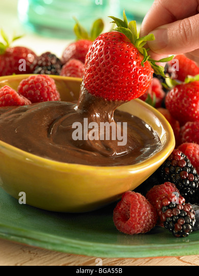 Strawberry dipping in chocolate sauce - Stock Image