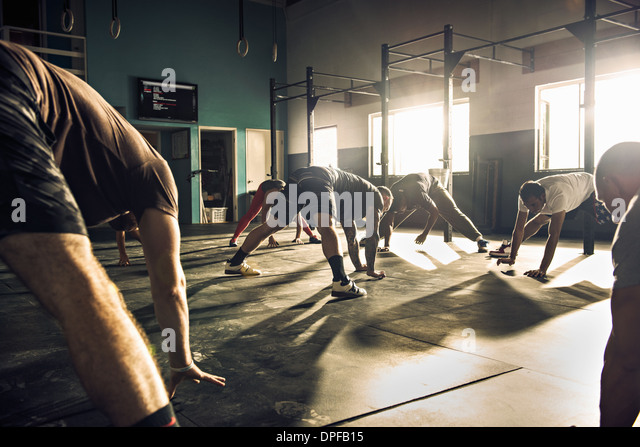 Fitness group training together in gym - Stock Image