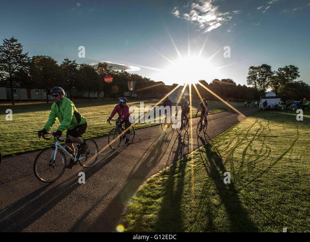 cyclists at dawn with sun rising over park - Stock Image