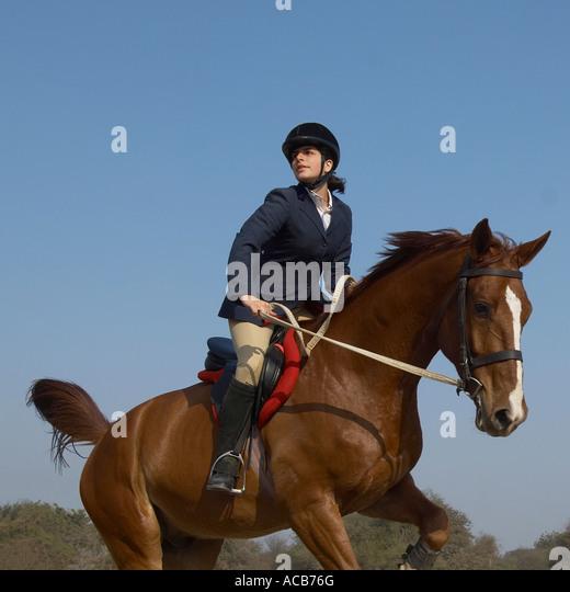 Female jockey riding a horse - Stock Image