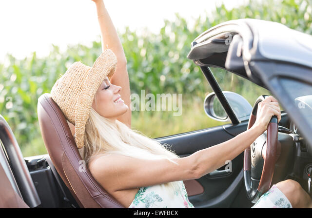 Side view of woman enjoying ride in convertible outdoors - Stock Image