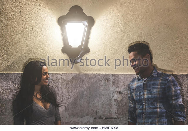 Couple in city at night, face to face, smiling - Stock-Bilder