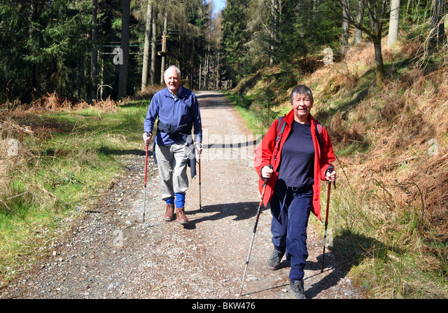 Active elderly people go hill walking in the Trossachs National Park, Scotland - Stock Image