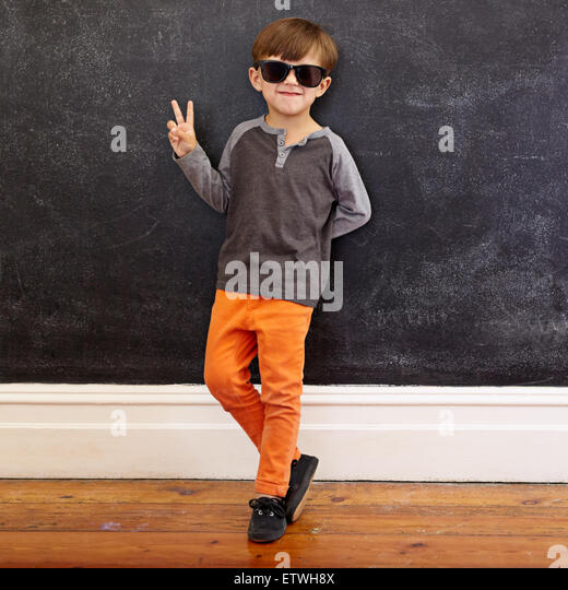 Full length shot of cool little boy wearing sunglasses gesturing victory sign. Young school boy in casuals showing - Stock-Bilder