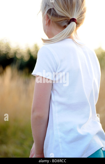 Royalty free photograph of a girl enjoying a summer evening camping in British national park and looking at sunset - Stock Image