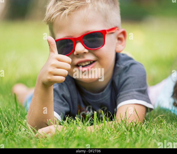 Portrait of smiling boy showing thumbs up gesture - Stock Image