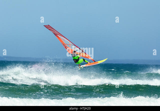 Windsurfer jumping over a big wave at Seven Mile Beach, Gerroa, Illawarra Coast, New South Wales, NSW, Australia - Stock-Bilder