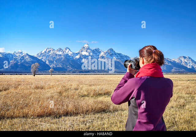 Rear view of a blurred woman taking pictures with DSLR camera in the Grand Teton National Park, focus on background, - Stock Image