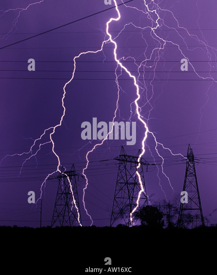 Lightning strikes against a dark purple sky near powerlines and power poles or electrical towers during a monsoon - Stock Image