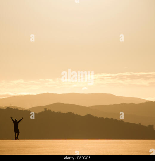 Silhouette of man in morning sun and view of landscape - Stock Image
