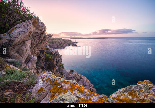 Seascape of the Italian coast at sunset with a lighthouse in the background. Porto Cervo - Emerald coast, Sardinia - Stock Image