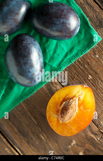Halved Plums with Green Napkin on Wood - Stock Image