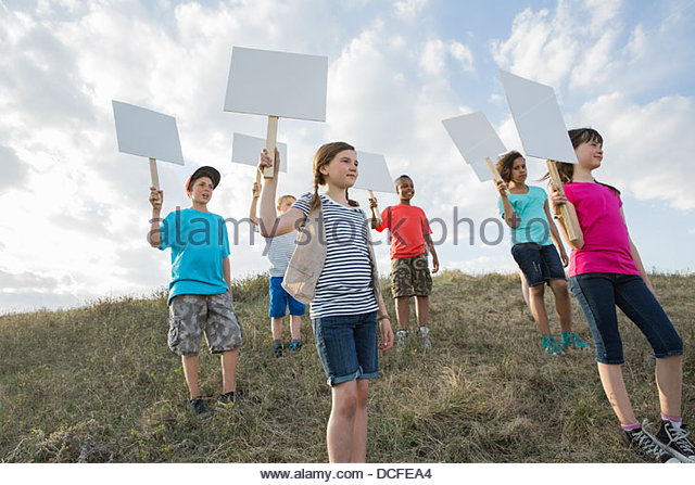 Schoolchildren holding blank billboards on hillside - Stock Image