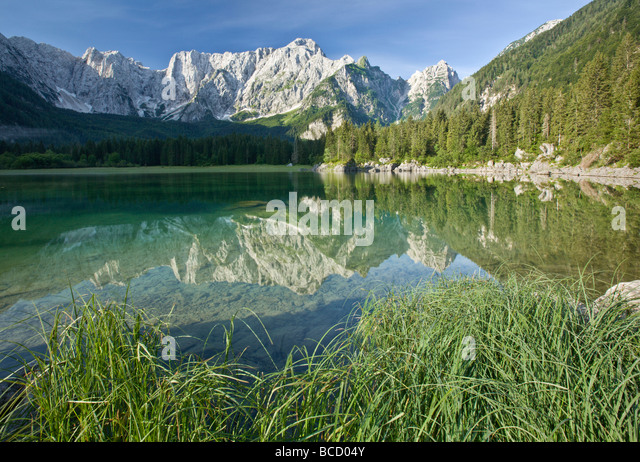 MANGRT MOUNTAIN reflected in lake at Lagi di Fusine. Julian Alps. Italy - Stock Image