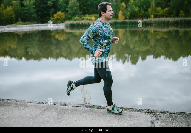 Man at the lake running against green cloudy nature - Stock-Bilder