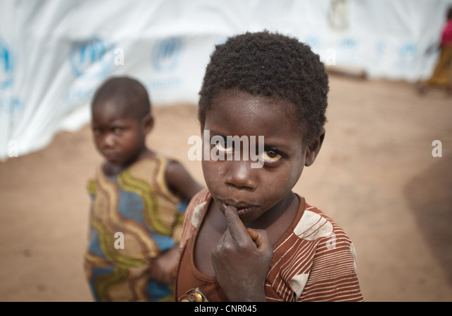 Children stand between basic shelters made of tarp at the Miketo IDP settlement, Katanga province, Democratic Republic - Stock-Bilder