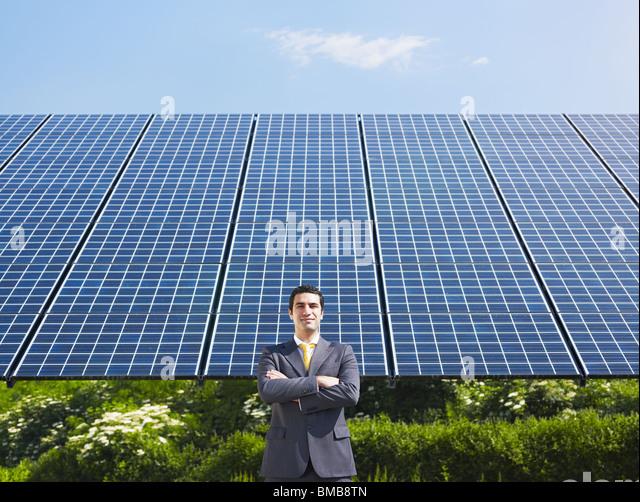 businessman standing near solar panels - Stock Image