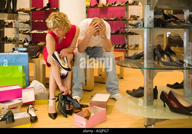 Man despairing as woman chooses shoes - Stock Image
