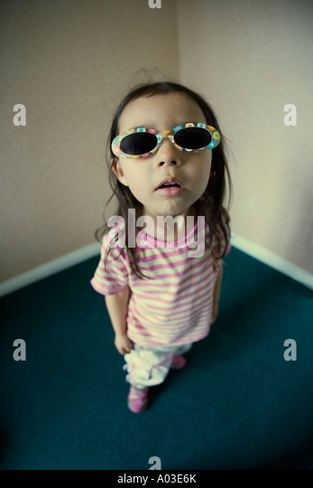 Cheeky girl with face up close wearing sunglasses - Stock Image