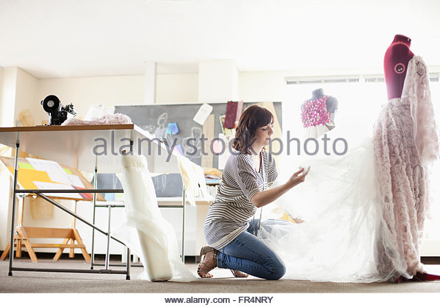 clothing designer fussing with material on form - Stock Image