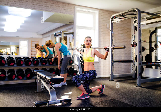 Women in gym exercising with weights and bar - Stock Image