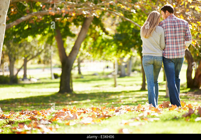 Rear View Of Romantic Couple Walking Through Autumn Woodland - Stock-Bilder