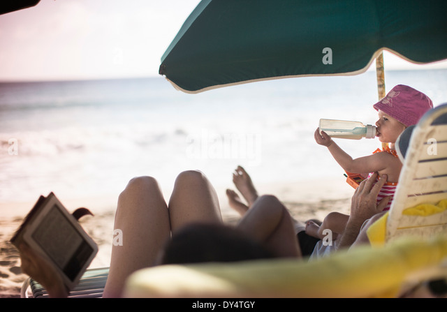 Family lying on sun loungers, reading and having a drink - Stock Image