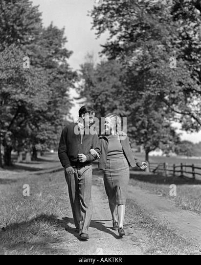 1930s 1940s YOUNG TEENAGE COUPLE BOY GIRL STROLLING DOWN AUTUMN COUNTRY LANE ARM IN ARM - Stock Image