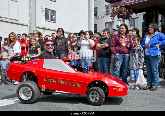 Man driving a micro car. 4th July parade. Juneau. Alaska. USA - Stock Image