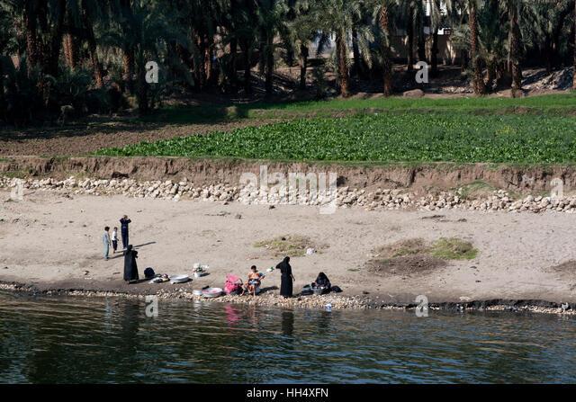 Women walk down to the Nile for laundry - Stock-Bilder