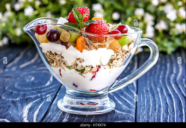 Fruit salad closeup with berries, yogurt and granola in a glass bowl on an old wooden board - Stock Image