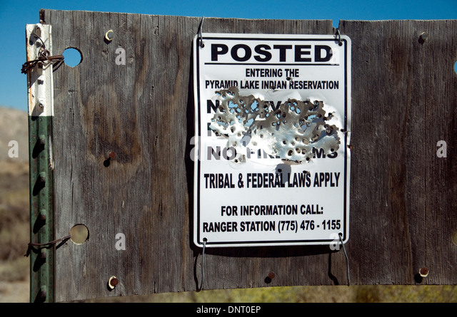 Bullet-holed sign for an Indian reservation in Nevada suggests target practice and displeasure - Stock Image