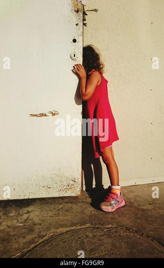 Side View Of Girl Peeking From Door - Stock Image