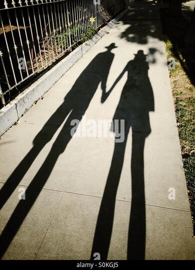 Shadows of a man and woman wearing shorts and hats - Stock Image