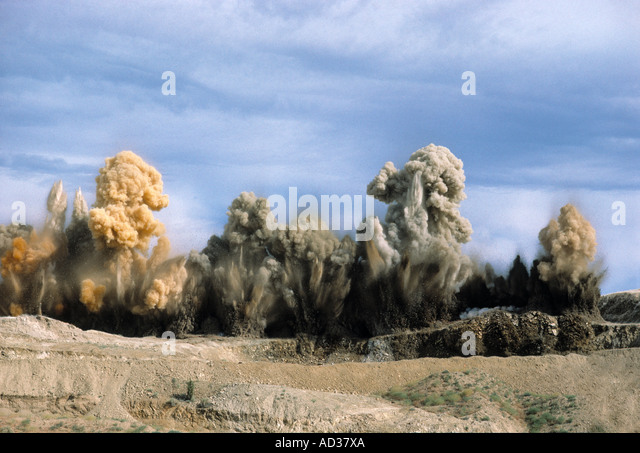 Explosion throws dirt into the sky at a mine. - Stock Image