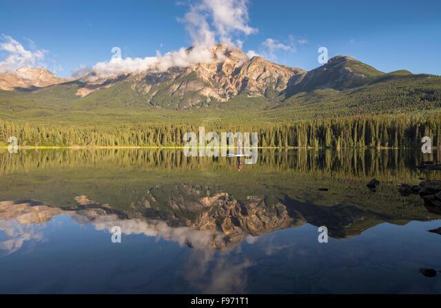 Reflection of Pyramid Mountain and woman paddle boarding on Pyramid Lake. Jasper National Park, Alberta, Canada. - Stock Image