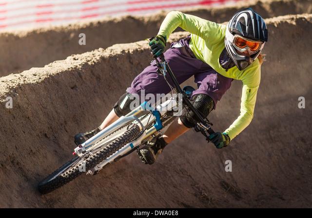 Young female mountainbiker racing in Sea Otter Classic Mountainbike Festival on Laguna Seca Raceway near Monterey - Stock Image