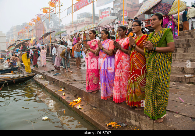 Five women in colorful saris in prayer, on the banks of the Ganges River, Varanasi, Uttar Pradesh, India - Stock-Bilder