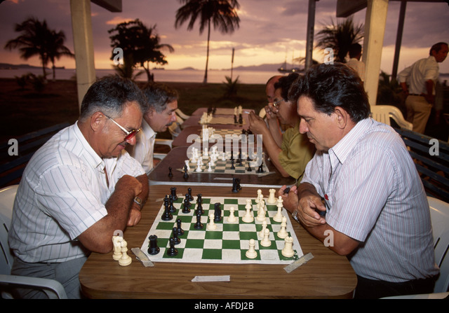 Venezuela Puerta la Cruz Caribbean Sea shore Hispanic men residents chess public park sunset - Stock Image