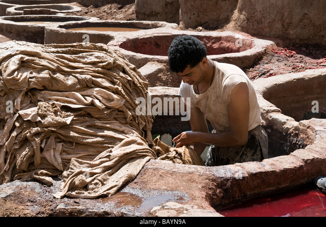 Worker stood up to his waist in a vat at the Chouara tannery in the medina. He is emptying the vat after stripping - Stock Image