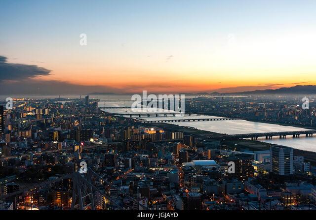 Japan, Osaka. Osaka and Kobe seen from top of Sky building. Yodogawa river with bridges at sunset with orange skies. - Stock Image