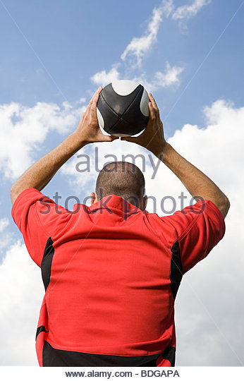 Rear view of a rugby player throwing a rugby ball - Stock Image