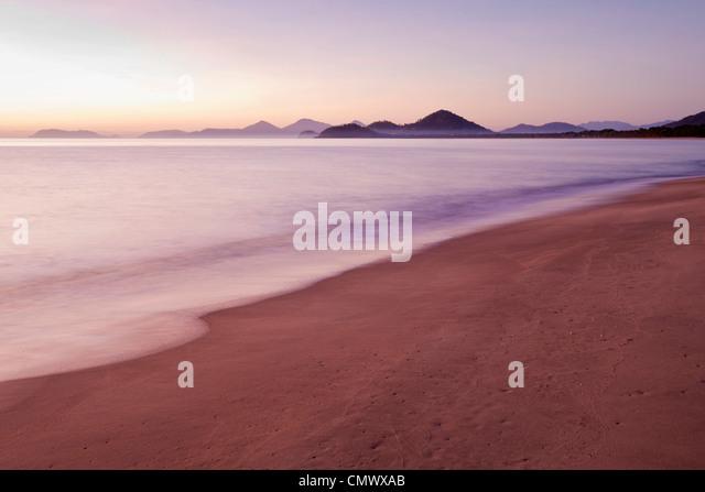 View along beach at dawn. Machans Beach, Cairns, Queensland, Australia - Stock Image