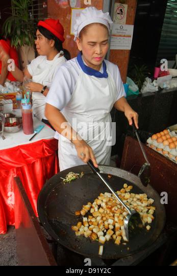 Bangkok Thailand Samphanthawong Chinatown Yaowarat Road Asian woman cook chef street food vendor cooking preparing - Stock Image