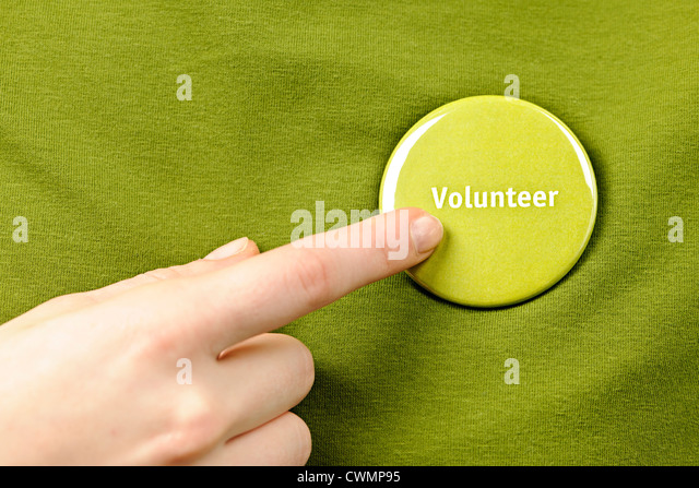 Finger pointing to green round volunteer button - Stock Image