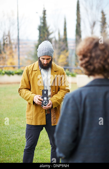 Young bearded hipster taking photo to redhead girl with TLR camera outdoors - Stock-Bilder